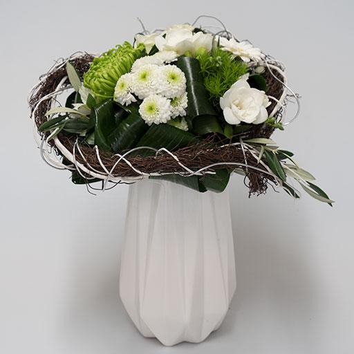 Ein Herzstrauß mit grünen und weißen Blumen in einer weißen Vase.