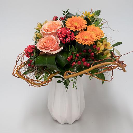 Ein Herzstrauß mit roten, orangenen, gelben, apricotfarbenen und grünen Blumen in einer weißen Vase.