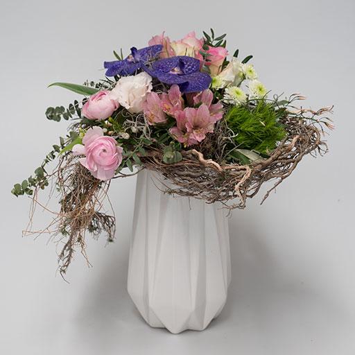 Ein Herzstrauß mit lila, pinken und weißen Blumen in einer weißen Vase. Umrahmt von Zweigen in einer Herzform.