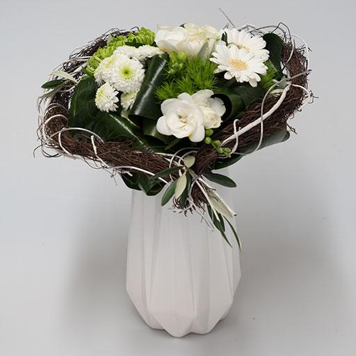 Ein Herzstrauß mit grünen und weißen Blumen, eingerahmt von braunen Zweigen in einer Herzform, in einer weißen Vase.