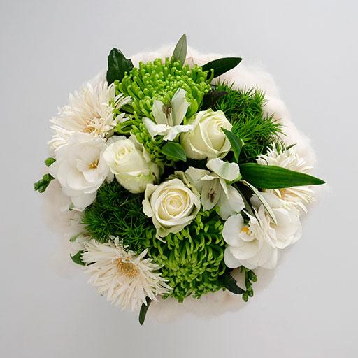Ein Neststrauß mit weißen und grünen Blumen, umringt von einem Nest aus weißer Watte, von oben.