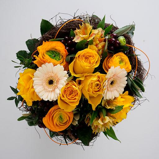 Ein Neststrauß mit gelben, orangenen, weißen und grünen Blumen von oben.