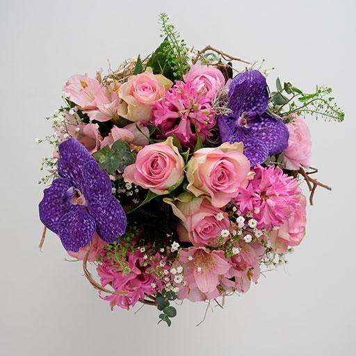 Ein Neststrauß mit lila, rosa, pinken und grünen Blumen von oben.