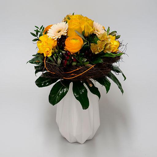 Ein Neststrauß mit gelben, orangenen, weißen und grünen Blumen, umringt von einem Nest aus Heu, in einer weißen Vase.