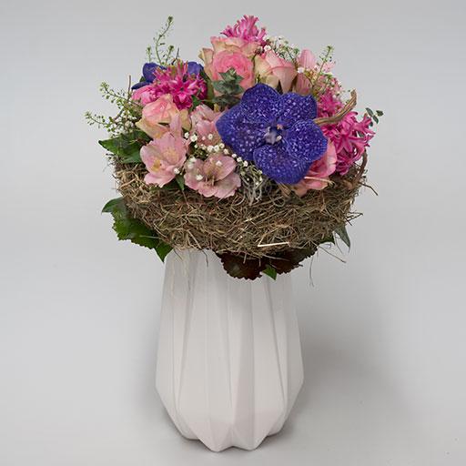 Ein bunter Neststrauß mit lila, rosa und roten Blumen, umringt von einem Nest aus Heu, in einer weißen Vase.