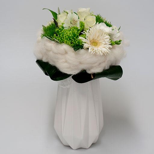 Ein Neststrauß mit weißen und grünen Blumen, umringt von einem Nest aus weißer Watte, in einer weißen Vase.