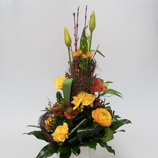 Ein Pyramidenstrauß mit gelben, orangenen und grünen Blumen in einer weißen Vase.