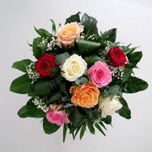 Ein Rosenstrauß mit roten, weißen, pinken und orangenen Rosen mit viel Grün von oben.