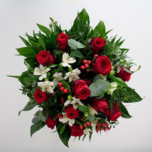 Ein Rosenstrauß mit roten Rosen, weißen Blüten und viel Grün von oben.