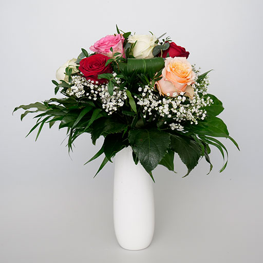 Ein Rosentrauß mit roten, weißen, pinken und orangenen Rosen sowie viel Grün in einer weißen Vase.