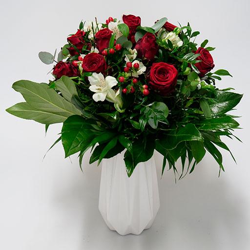 Ein klassischer Rosenstrauß mit roten Rosen, weißen Blüten und viel Grün in einer weißen Vase.