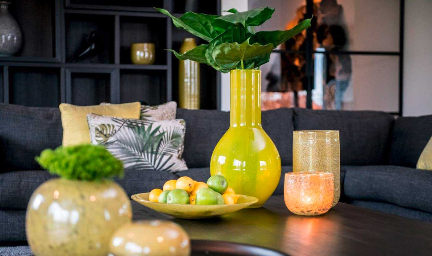 Accessoires im Wohnzimmer: Auf einem braunen Holztisch stehen eine gelbe Vase mit einer grünen Pflanze, 2 Kerzengläser und eine gelbe Schale mit grünen Äpfeln und Zitronen.