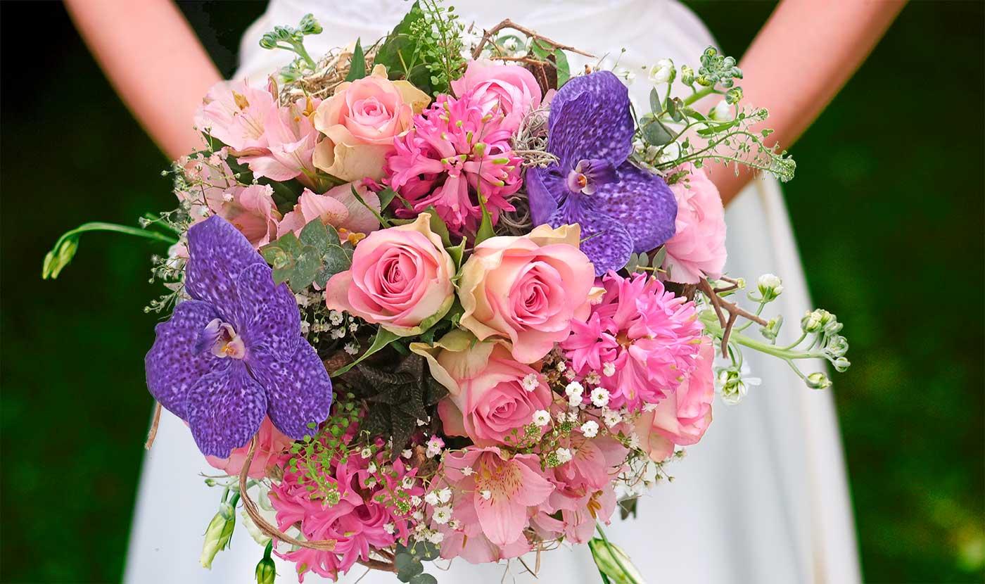 Nahaufnahme eines bunten Blumenstraußes mit lila, rosa und weißen Blüten. Man sieht die Arme einer Frau im weißen Kleid, die das kunstvolle Stück Floristik in Händen hält.