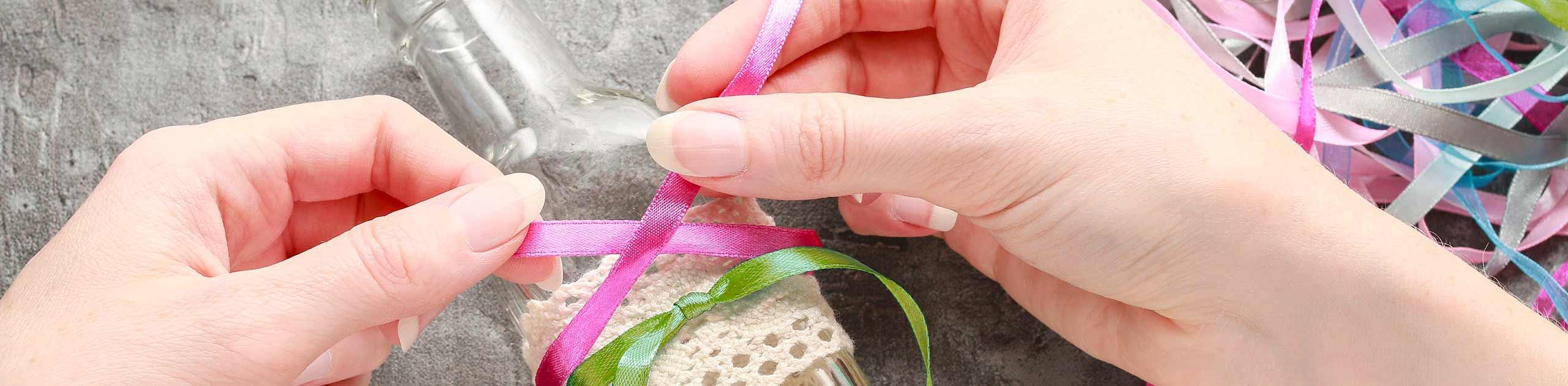 2 Frauenhände binden eine pinke Schleife um eine Flasche. Dort ist bereits eine grüne Schleife befestigt. Im oberen rechten Eck liegen viele verschiedenfarbige Schleifen durcheinander.