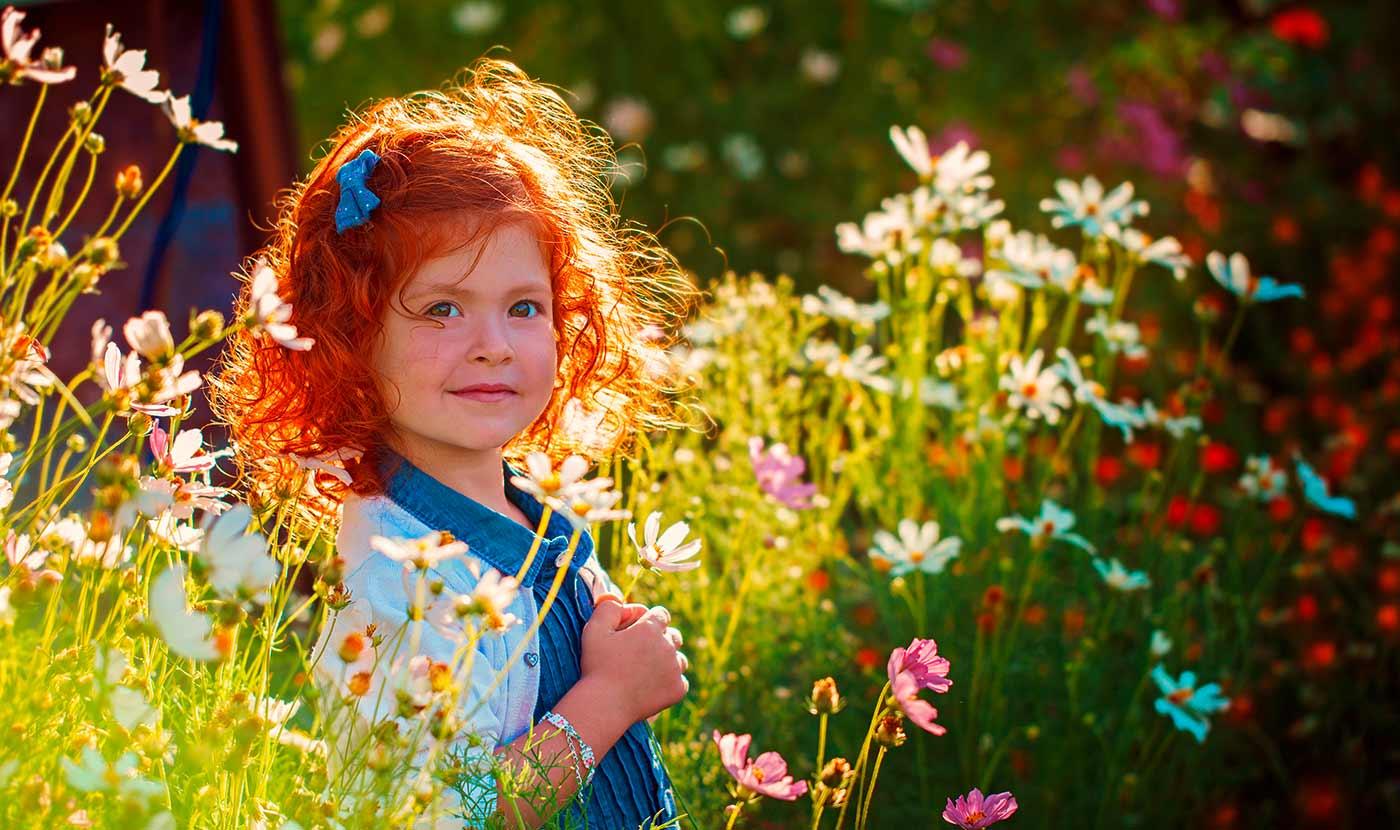 Ein Mädchen mit roten Haaren steht in einem Garten voller grüner, weißer, roter und lilafarbener Blumen. Die Blumen sind hochgewachsen und überragen das Mädchen teilweise.